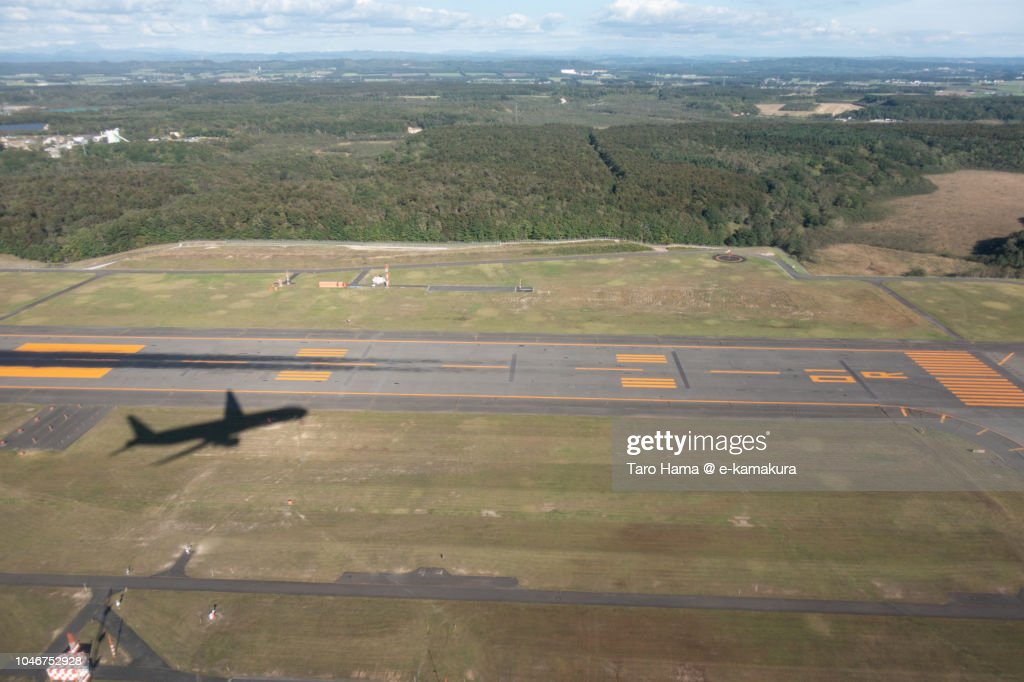 The silhouette of airplane taking off Hokkaido New Chitose Airport (CTS) in Japan daytime aerial view from airplane : ストックフォト