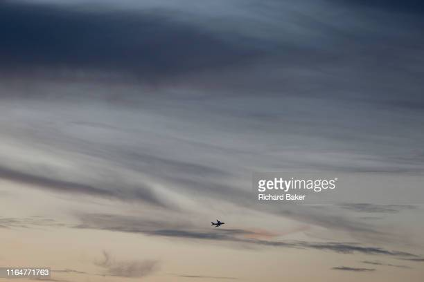 The silhouette of an airliner that has taken off from Heathrow Airport to the west and overflying the capital amid high altitude soft clouds in a...