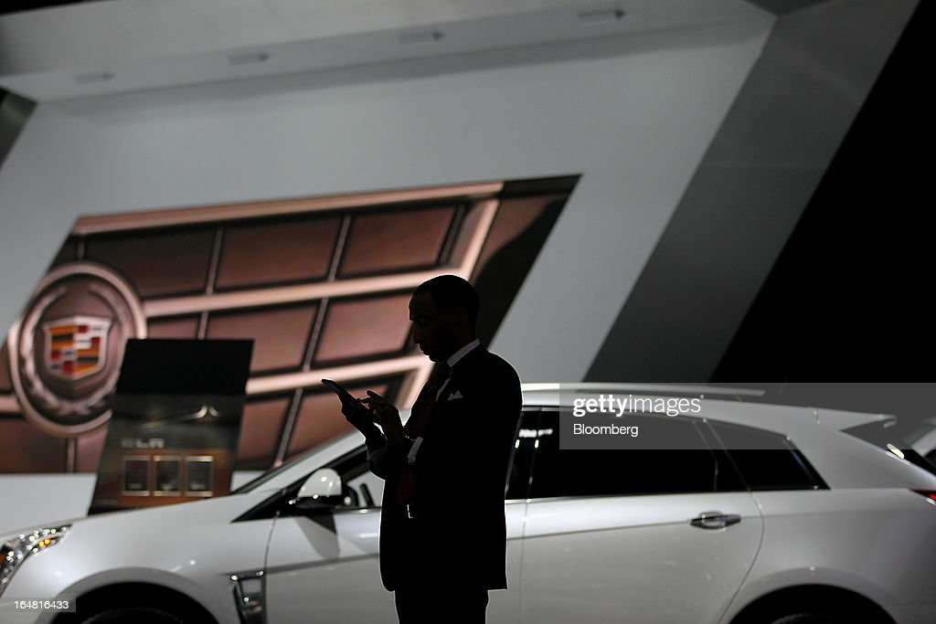 The silhouette of an attendee is seen at the General Motors Co. (GM) Cadillac booth during the 2013 New York International Auto Show in New York, U.S., on Thursday, March 28, 2013. The 113th New York International Auto Show, which runs from March 29 to April 7, features 1,000 vehicles as well the latest in tech, safety and innovation. Photographer: Jin Lee/Bloomberg via Getty Images