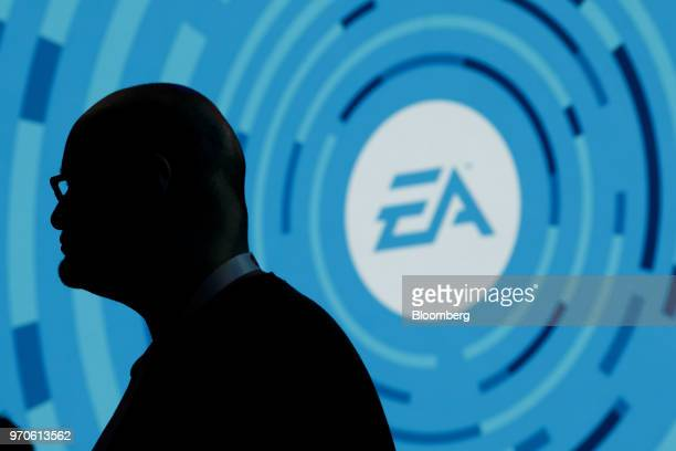 The silhouette of an attendee is seen standing in front of a Electronic Arts Inc logo displayed on a screen during the company's EA Play event ahead...