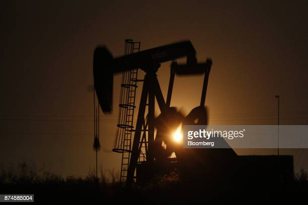 The silhouette of an electric oil pump jack is seen at dusk in the oil fields surrounding Midland Texas US on Tuesday Nov 7 2017 Nationwide gross oil...