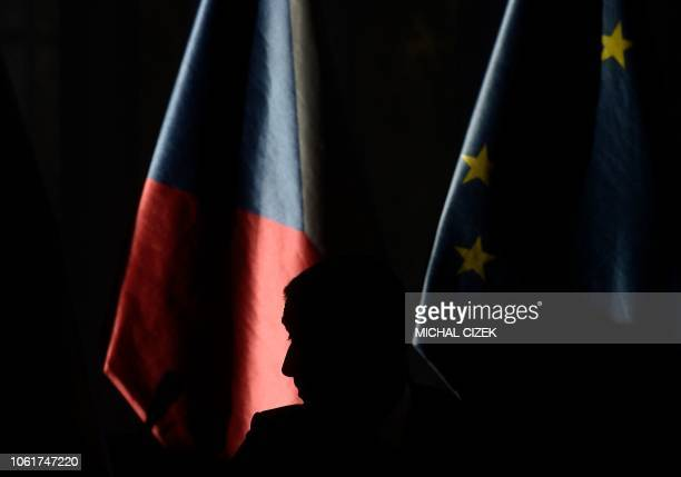The silhouette of Czech Prime Minister Andrej Babis is seen as he walks past an European and a Czech flag before a joint meeting between the Czech...