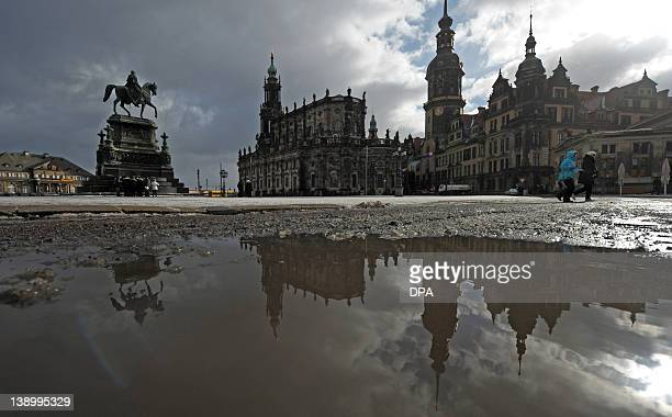 The silhouette of Dresden is reflected in a puddle LR The monument of King John the Hofkirche and the Castle on February 15 2012 in Dresden eastern...
