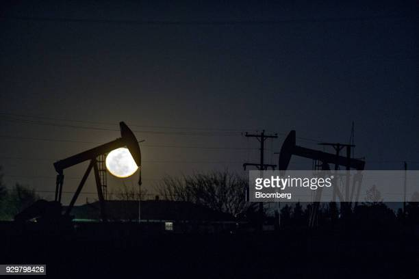 The silhouette of pumpjacks are seen as the moon rises in the Permian Basin near Midland Texas US on Friday March 2 2018 Chevron the world's...