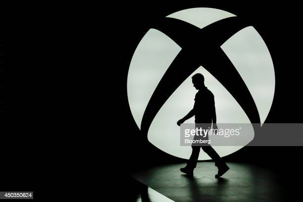The silhouette of Ralph Fulton design director for Forza Horizon at Playground Games is seen walking past the Microsoft Corp Xbox One logo uring a...