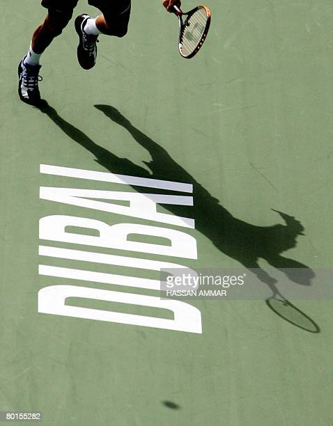 The silhouette of Russian Nikolay Davydenko is reflected on the ground as he returns the ball to Spain's Feliciano Lopez during their semifinal...