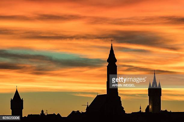 The silhouette of Straubing southern Germany is pictured during a colorful sunrise on November 22 2016 / AFP / dpa / Armin Weigel / Germany OUT