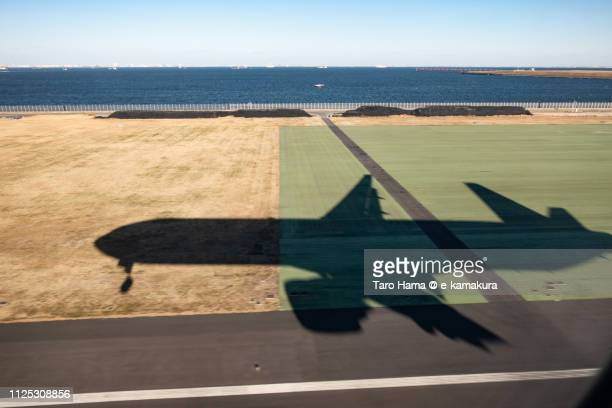 The silhouette of the airplane landing on Tokyo Haneda International Airport (HND) in Tokyo in Japan daytime aerial view from airplane