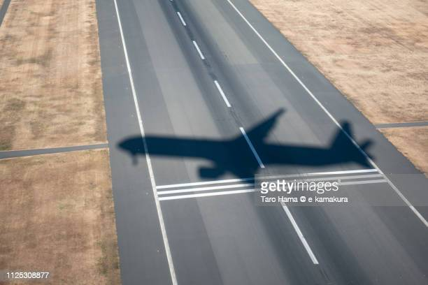 the silhouette of the airplane landing on tokyo haneda international airport (hnd) in tokyo in japan daytime aerial view from airplane - %e... ストックフォトと画像