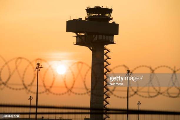 The silhouette of the control tower of the Berlin Brandenburg Airport and barbed wire are pictured at sunset in Schoenefeld Germany on April 14 2018