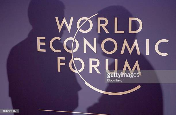 The silhouette of two delegates speaking is cast over the World Economic Forum logo prior to a plenary session at the WEF's India Economic Summit in...