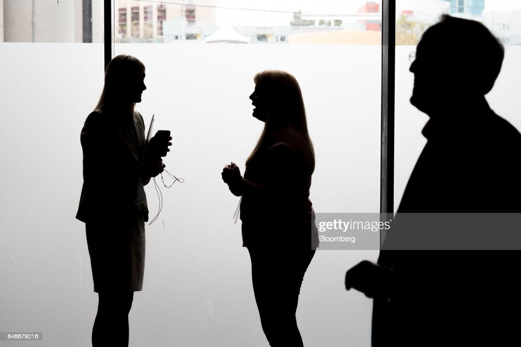 The silhouettes of attendees are seen as they speak outside a conference room during the Mobile World Conference Americas event in San Francisco, California, U.S., on Wednesday, Sept. 13, 2017. Leaders from the mobile ecosystem will be presenting the challenges and opportunities in the industry and the impact it has on society. Photographer: David Paul Morris/Bloomberg via Getty Images