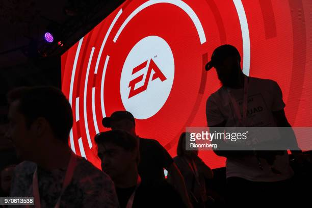 The silhouettes of attendees are seen standing in front of a Electronic Arts Inc logo displayed on a screen during the company's EA Play event ahead...