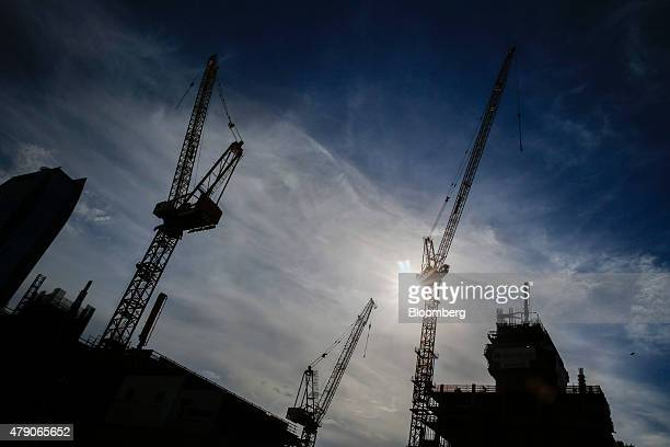 The silhouettes of cranes are seen standing above a construction site in downtown Los Angeles California US on Monday June 29 The US Census Bureau is...