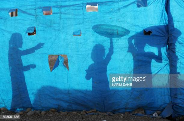 TOPSHOT The silhouettes of Iraqi children are seen on tarpaulin as they collect water from a tank at the AlKhazir camp for internally displaced...