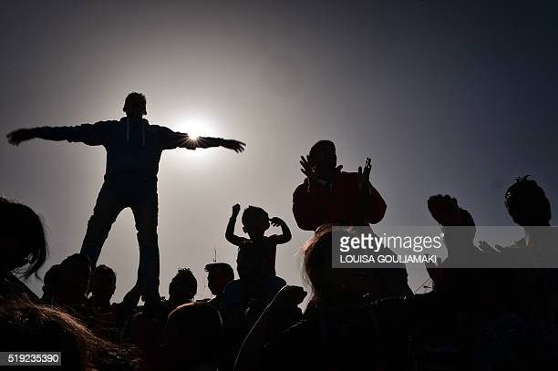 The silhouettes of Kurdish refugees who managed to leave the VIAL detention center on the island of Chios are seen as they protest against...