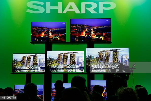 The silhouettes of media members are seen in front of Sharp Corp 4K UHD LED televisions after a press conference during the 2015 Consumer Electronics...