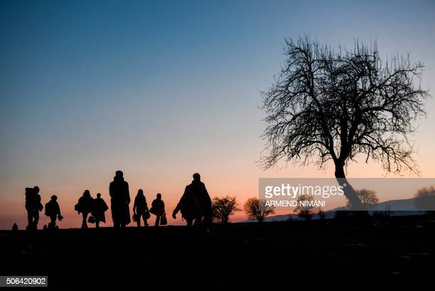 TOPSHOT The silhouettes of migrants and refugees are seen as they walk after crossing the Macedonian border into Serbia near the village of Miratovac...