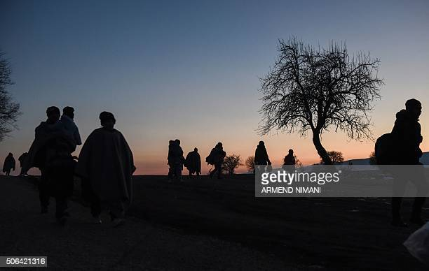 The silhouettes of migrants and refugees are seen as they walk after crossing the Macedonian border into Serbia near the village of Miratovac on...