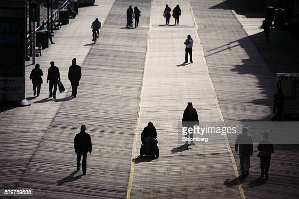 The silhouettes of pedestrians are seen walking along the boardwalk in Atlantic City New Jersey US on Monday May 2 2016 Atlantic City made $18...