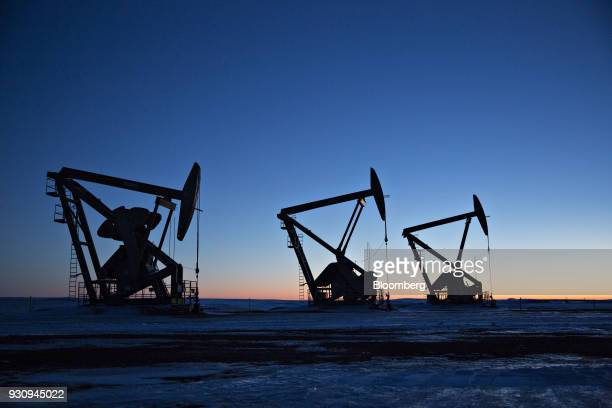 The silhouettes of pumpjacks are seen above oil wells in the Bakken Formation near Dickinson North Dakota US on Wednesday March 7 2018 When oil sold...