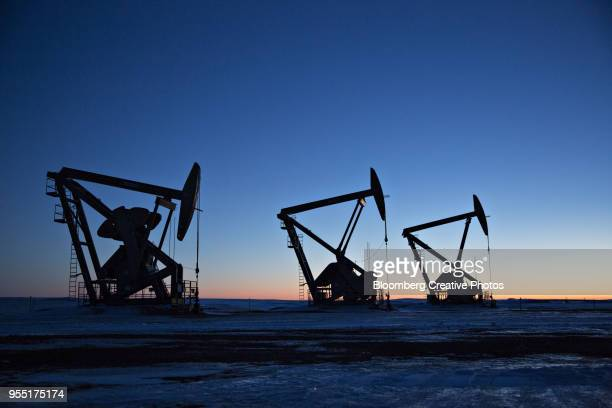 the silhouettes of pumpjacks are seen above oil wells in the bakken formation - oil stock pictures, royalty-free photos & images