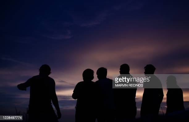 The silhouettes of tourists are seen against the sky after sunset at the top of the Cerro Quezalapa in Canton Barahona, San Pedro Masahuat, 50 km...