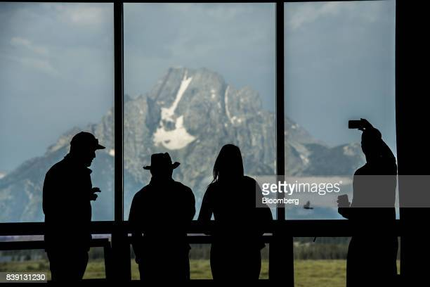 The silhouettes of tourists are seen viewing the Grand Teton mountain range outside of the Jackson Lake Lodge during the Jackson Hole economic...