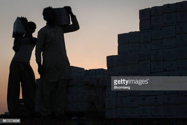 The silhouettes of workers are seen as they load boxes of tiles onto a truck at the Shabbir Tiles Ceramics Ltd production facility at dusk in Karachi...
