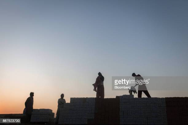The silhouettes of workers are seen as they stand on boxes of tiles stacked on trucks at the Shabbir Tiles Ceramics Ltd production facility at dusk...