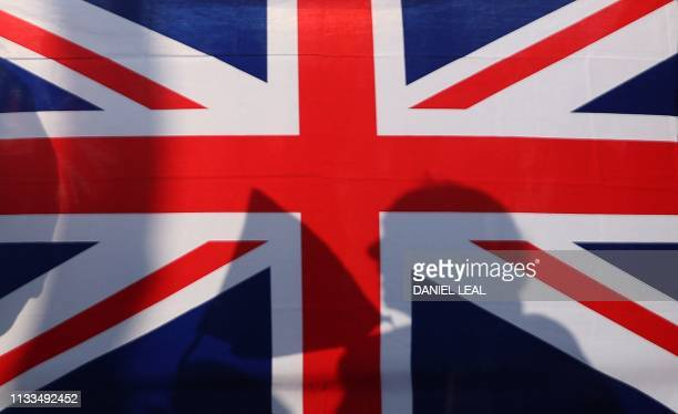 The sillouette of a proBrexit demonstrator is seen through a Union Flag held up in Parliament Square outside the House of Commons in central London...