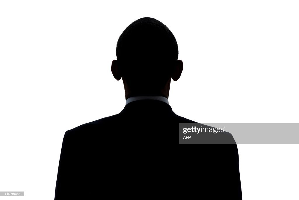 The sillouette of US President Barack Obama is seen as he reviews the honour guard during the welcoming ceremony at Planalto Palace in Brasilia, on March 19, 2011. Obama is on a two-day visit to Brazil as part of a tour that includes Chile and El Salvador. AFP PHOTO/Pedro SANTANA