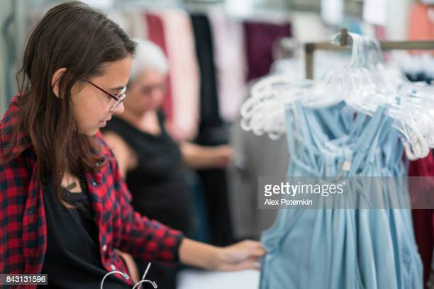 the silver-haired 65-years-old active senior woman and her teenager granddaughter shopping in the clothing retail store - 14 15 years stock pictures, royalty-free photos & images