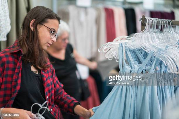 銀髪 65 歳アクティブ シニア女性とティーンエイ ジャー孫娘、衣料品小売店でのショッピング