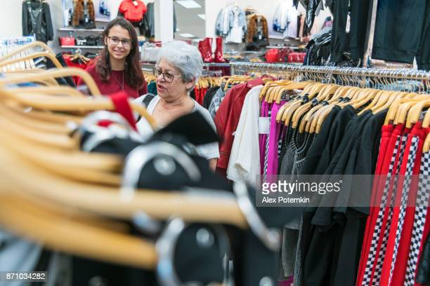 the silver-haired 65-years-old active senior woman and her teenager granddaughter shopping in the clothing retail store - 65 69 years stock pictures, royalty-free photos & images