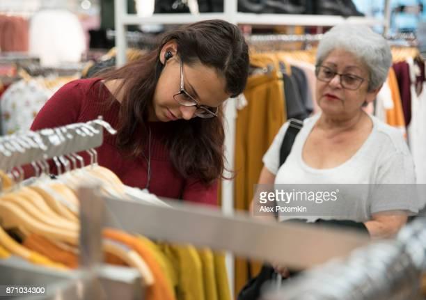 銀髪 65 歳アクティブ シニア女性とティーンエイ ジャー孫娘、衣料品小売店でのショッピング - 16 17 years ストックフォトと画像