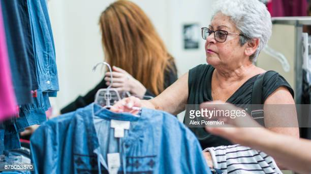 the silver-haired 65-years-old active senior woman and her teenager granddaughther shopping in the clothing retail store - 65 69 years stock pictures, royalty-free photos & images