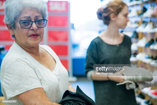 the silver-haired 65-years-old active senior woman and her teenager granddaughter shopping in the shouse retail store - 65 69 years stock pictures, royalty-free photos & images