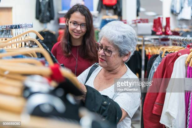 the silver-haired 65-years-old active senior woman and her teenager granddaughter shopping in the clothing retail store - 16 17 years photos stock photos and pictures