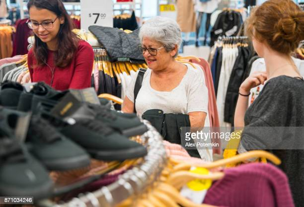 the silver-haired 65-years-old active senior woman and her two teenager granddaughters, sisters, shopping in the clothing retail store - 65 69 years stock pictures, royalty-free photos & images