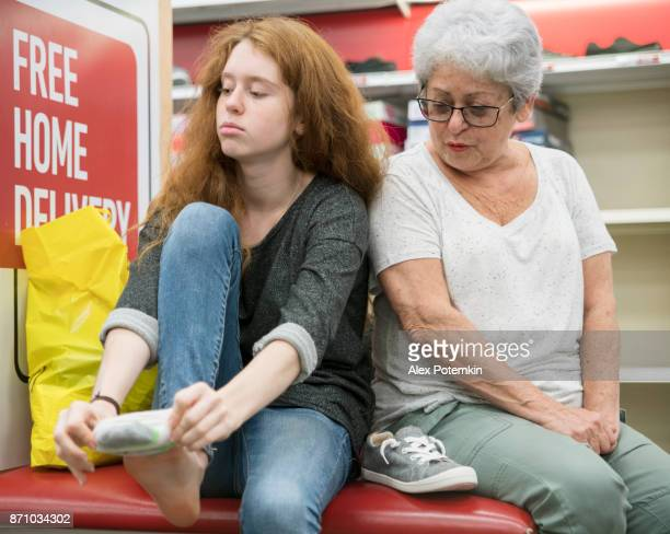 the silver-haired 65-years-old active senior woman and her unhappy teenager granddaughter shopping shoes in the clothing retail store - 65 69 years stock pictures, royalty-free photos & images