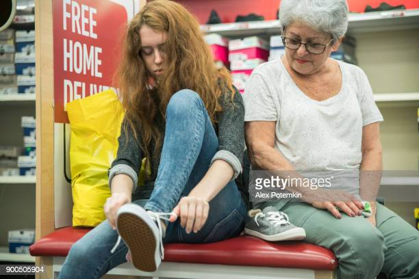 The silver-haired 65-years-old active senior woman and her unhappy teenager granddaughter shopping shoes in the clothing retail store