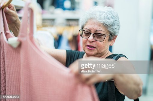 The silver-haired 65-years-old active senior woman shopping in the clothing retail store