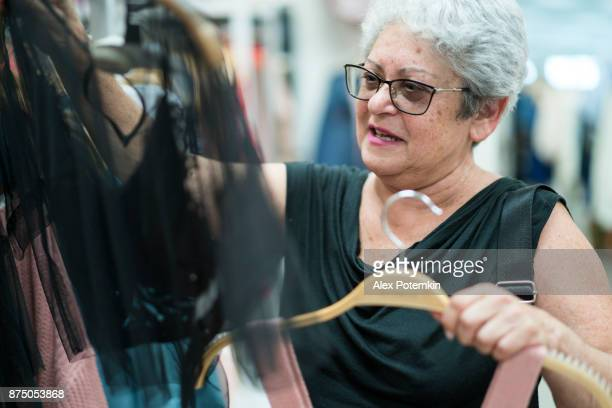 the silver-haired 65-years-old active senior woman shopping in the clothing retail store - 65 69 years stock pictures, royalty-free photos & images