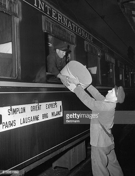 4/9/1951 The SimplonOrient Express will start its long journey in a few minutes Here a man hands a hat bag to a porter on the train