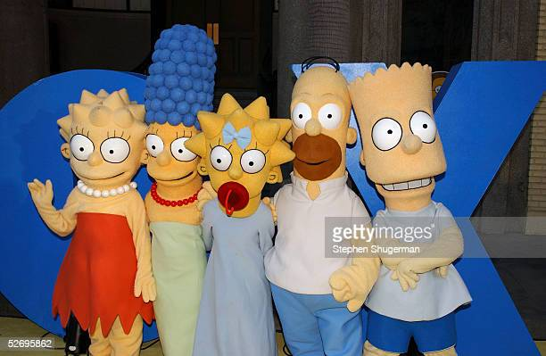 The Simpsons characters Lisa Marge Maggie Homer and Bart Simpson pose for a photograph at The Simpsons 350th episode block party on the New York...