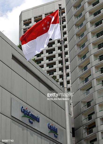 The Singapore flag flies on a pole next to a building with the sign of the CapitaLand subsidiaries company in Singapore on February 19 2009...