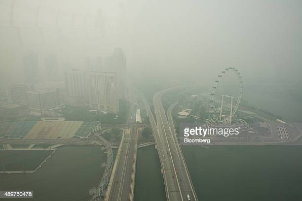 The Singapore Flyer Ferris wheel, right, stands shrouded in smog in Singapore, on Thursday, Sept. 24, 2015. The haze from Indonesian forest fires...