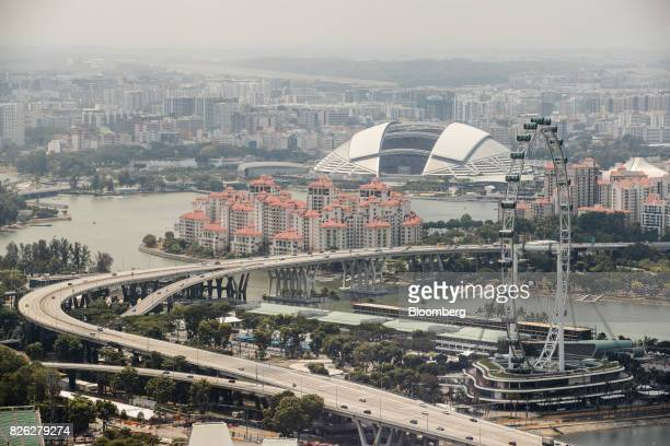 The Singapore Flyer Ferris wheel right the Singapore National Stadium second right and the Costa Rhu residential development stand in Singapore on...