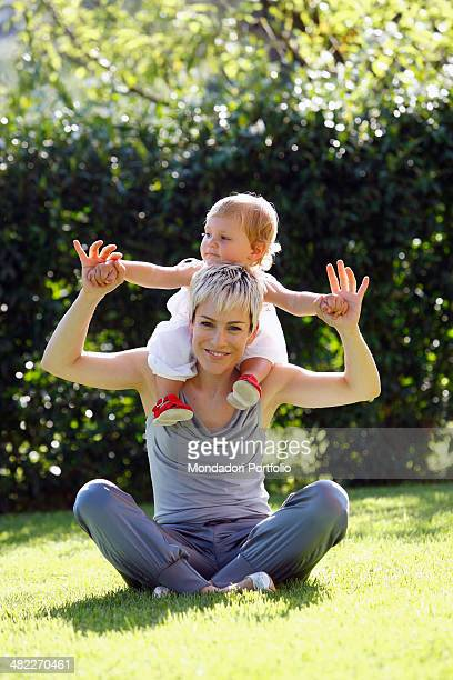 The singer Alexia native from La Spezia sits on the lawn with crossed legs with her 18monthold baby girl Maria Vittoria mother and daughter pose...